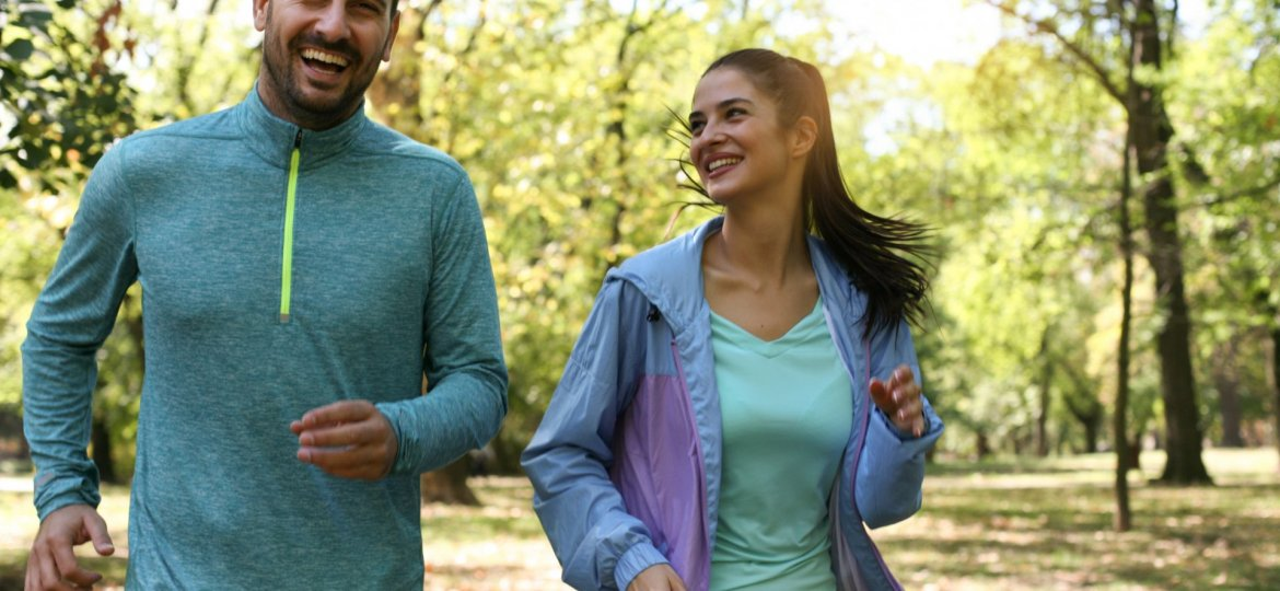 Young couple running together in park. Young people exercising.